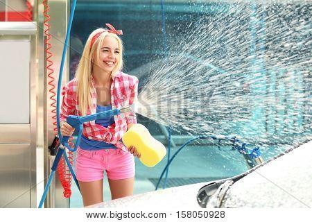 Woman washing car with high pressure foam