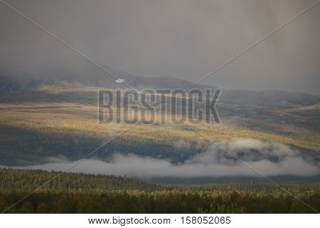 Sunlight giving golden glow to the autumn colored forest while moody clouds shrouding the landscape