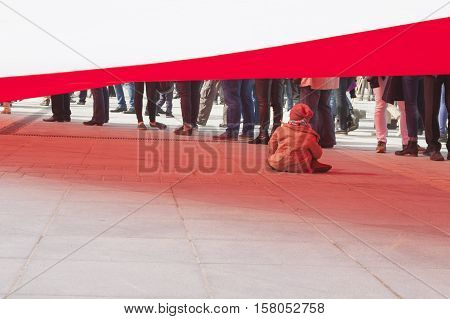 Little girl playing under a immense size flag of Poland carried by hundreds of people