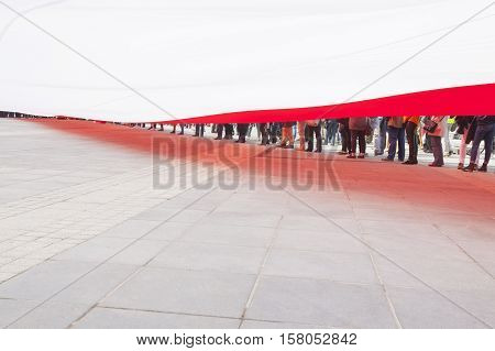 Immense size flag of Poland carried by hundreds of people during a political rally seen from underneath