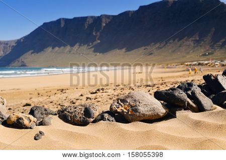 a view of the Famara Beach in Lanzarote, Canary Islands, Spain, with the Famara massif in the background