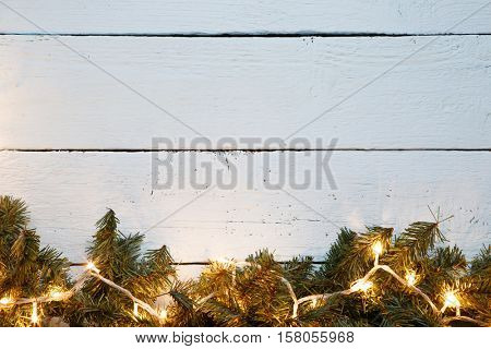 Wooden surface decorated with fir branches and lightbulb. Christmas card