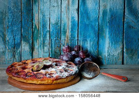 Plum cake fresh plums and a strainer old blue background space for text