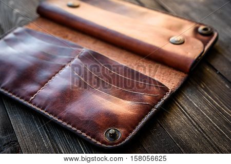 Brown leather wallet on wooden table, Old leather wallet.