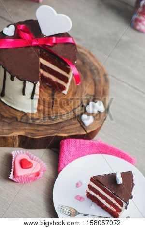 Slice of a red velvet cake with white hearts on top and pink ribbon as a Valentine Day present