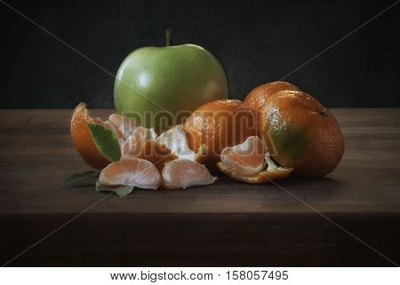 green apple and tangerine on a wooden table on a dark background