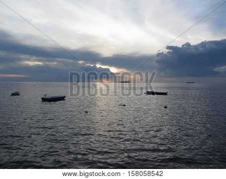 Warm sea sunset with cargo ships and small fishing boats at the horizon . Giants cumulonimbus clouds are in the sky. Tuscany Italy