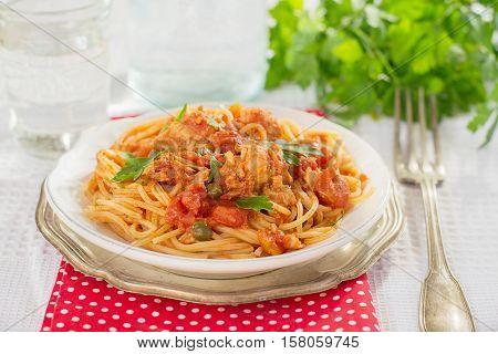 Pasta spaghetti with tuna capers and parsley in tomato sauce