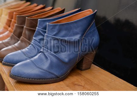 Women's leather boots on wooden table Shoe shop -