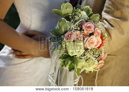 Newly married pair with bouquet close up