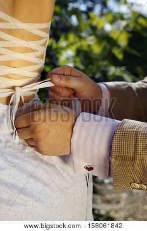 The groom helps the bride to tie a ribbon on the dress