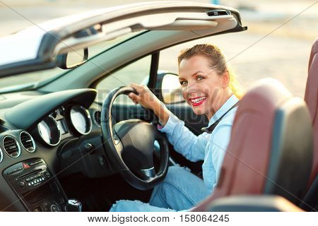 Young pretty woman sitting in a convertible car - concept of buying a used car or a rental car
