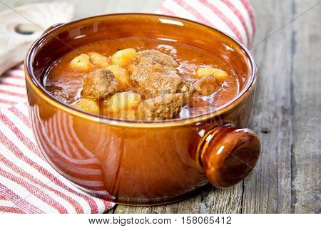 goulash in brown bowl on wooden table