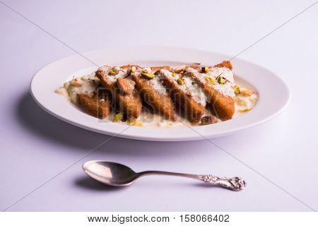 Shahi Tukda prepared - deep fried bread in ghee, garnish with sweetened cream and dry fruits.