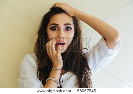 Close-up portrait of young woman scared, afraid and anxious biting her finger nails, looking straight into camera with wide opened eyes isolated on yellow background. Human emotions concept. Copy space text.