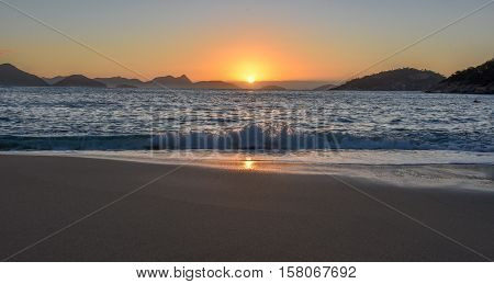 Beautiful Sunrise with the sun rising out of the ocean at the Red Beach, Praia Vermelha, with the Sugarloaf Mountain, Rio de Janeiro