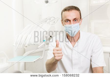 Portrait of dentist in a medical mask showing thumbs up which is in the workplace in the dental clinic