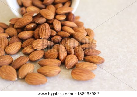 Almonds spilling out of a container on a kitchen countertop. Close-up image with point of interest positioned left.