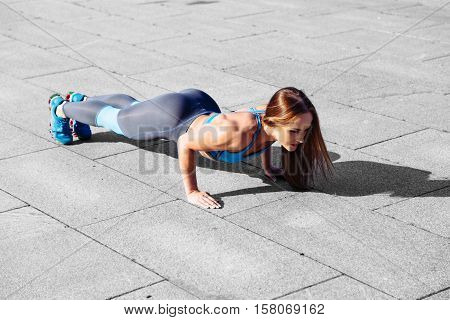 Fitness woman doing push-ups during outdoor cross training workout. Beautiful young and fit fitness sport model training outside in gray background. Copyspace text.