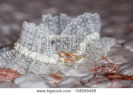 Decorated wedding garter with two golden rings, closeup. Marriage concept.