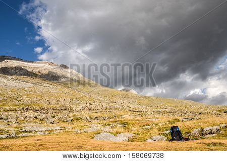Backpack and walking sticks left to rest on a mountain with clouds overhead