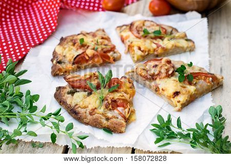 Wholewheat wholemeal pizza with tomatoes cheese and herbs