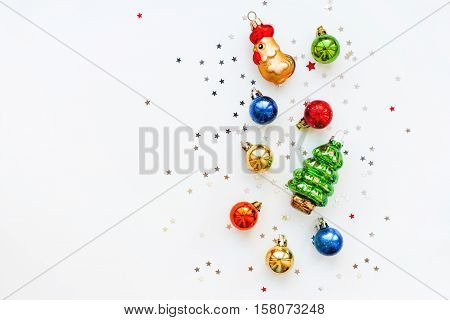 Christmas background with decorations. New Year 2017 symbol - Fire Rooster.Shiny colorful balls fir tree and star confetti. Flay lay top view.