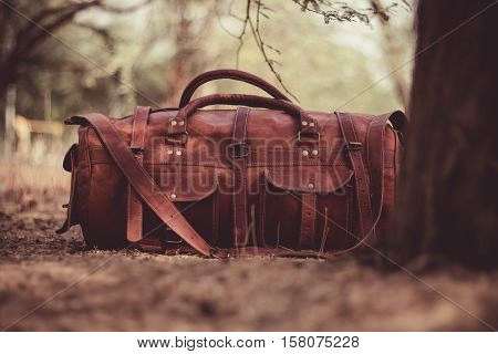 brown leather pocketed satchel with shoulder strap on ground