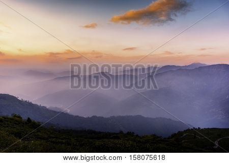Sunset sets behind the mountains as mist engulfs the region slowly