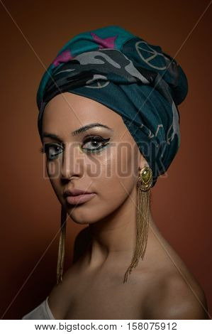 Beautiful woman with turban. Young beautiful woman with turban and golden accessories. Attractive fashionable girl with head wrapped in turban. Pretty Caucasian model wearing  earrings  posing in studio.