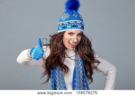Winter fashion. Young  woman wearing fashionable wintertime clothes white fur scarf  and gloves, studio shot