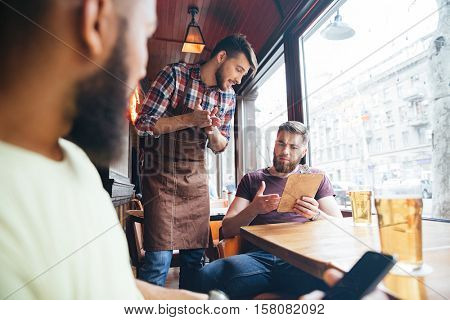 Angry irritated bearded man arguing with waiter about his bill in bar