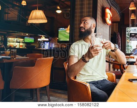 Two relaxed bearded men sitting in bar and ordering one more glass of beer