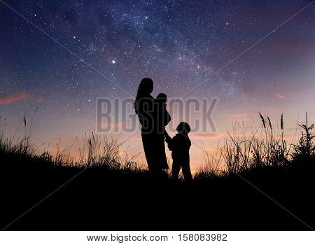 Silhouette of mother and her two little children against starry night sky