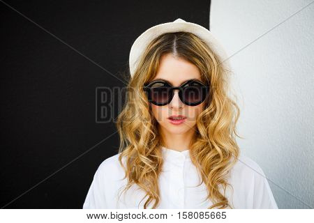 Close Up Portrait of Hipster Girl in Hat and Sunglasses on Contrast Black and White Wall Background. Urban Fashion Woman Outdoors in Summer. Street Style. Toned Photo with Copy Space.