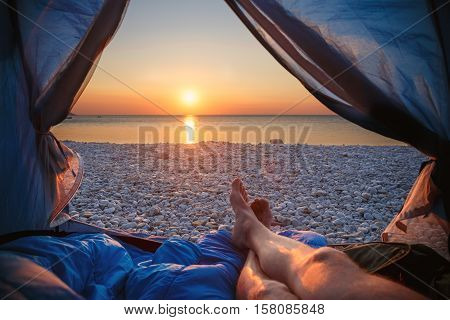 Image human legs lying in tourist tent with view of the sunset sea. Shallow DOF. Focus on pebble.