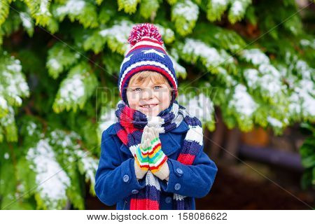 Funny little kid boy in colorful clothes playing outdoors during snowfall. Active leisure with children in winter on cold snowy days. Happy child having fun and playing with snow