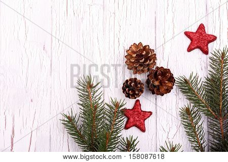 Shiny Red Stars,cones And Spruce Twigs Lying On White Floor