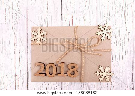 Wooden Number 2018 Lies On Simple Grey Present Box Decorated With Wooden Snowflakes