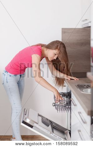 Beautiful Young Woman Made Up The Dishes In The Dishwasher.