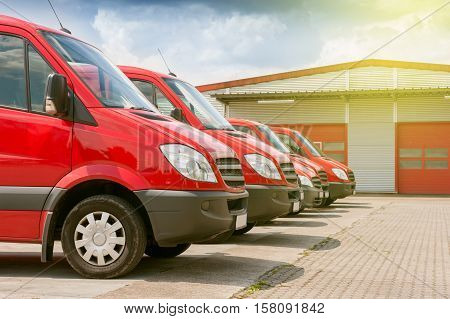 Business row of red delivery and service cars in front of a factory and warehouse distribution plant ready to pick-up the parcels boxes for delivery