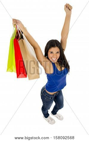 young happy and beautiful hispanic woman holding color shopping bags smiling excited isolated on white background in shopaholic fashion sales and consumerism concept