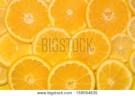Fresh oranges and lemons background. Yellow food background. Juicy slices of orange and lemon. Top view