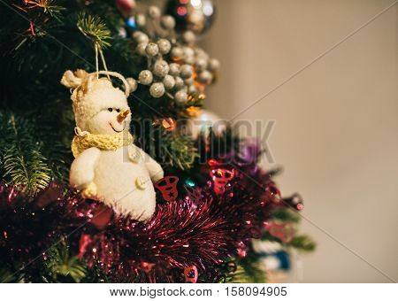 Closeup of tinsel and a snowman ornament hanging from the branches of a Christmas tree in a home during the festive season