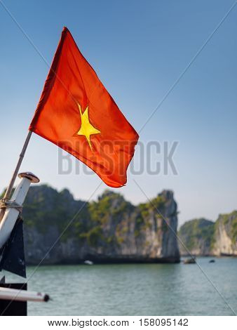 The flag of Vietnam (red flag with a gold star) fluttering on blue sky background in the Halong Bay at the Gulf of Tonkin of the South China Sea Vietnam. Landscape formed by karst isles.