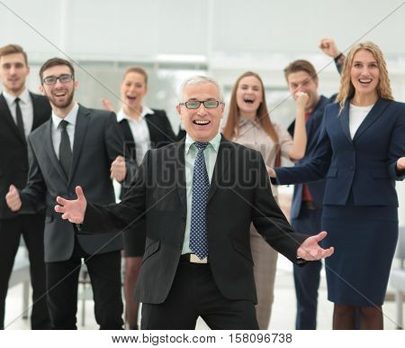 Mature businessman and cheerful business team on office backgrou