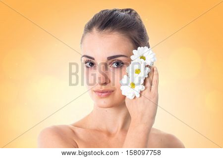 pretty girl takes care her skin with white flowers in hands isolated in studio. Health care concept. Body care concept. Young woman with healthy skin.