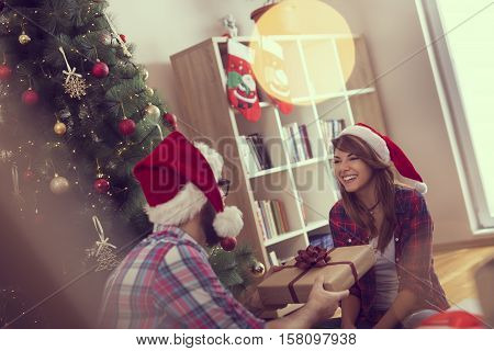 Couple in love sitting on a living room floor next to a nicely decorated Christmas tree exchanging Christmas presents and having fun