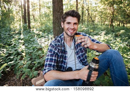 Guy drinking tea in forest. looking at camera. so happy