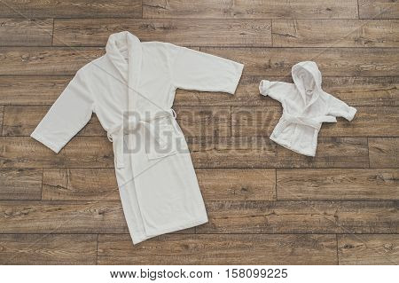 adult and children's white robes lying on the wooden background and are drawn to each other